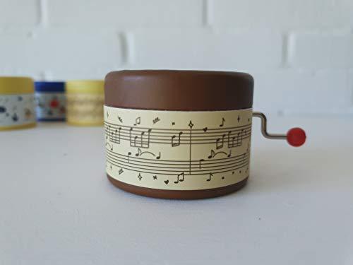 Caja de música marrón decorada con escritura musical y la melodía El lago de los cisnes en manivela manual