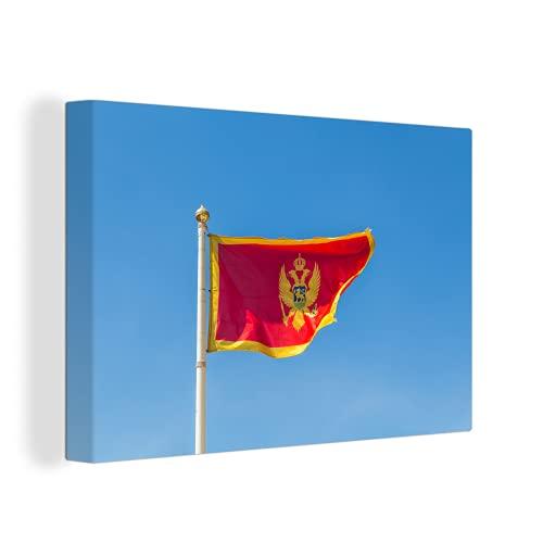 Leinwandbild - Flagge von Montenegro gegen einen klaren blauen Himmel abgebildet - 60x40 cm