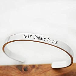 "A Goldendoodle gift that's a silver bracelet that says, ""Talk Doodle to Me,"" photo"