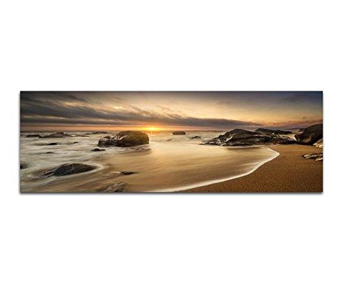 Paul Sinus Art Panoramabild auf Leinwand und Keilrahmen 150x50cm Meer Strand Steine Sonnenaufgang Wolken