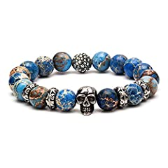 Size: 6.5 Inches. Material: 16 natural blue Regalite Beads with 1 Stainless Steel Skull, 1 Pentacle Ball, 4 Flower Ring. A special beaded bracelet for men and women. Regalite bead bracelet brings courage and strengthens faith, clear the mind. The ske...