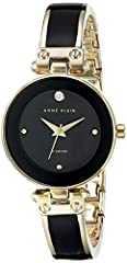 Mineral crystal lens; glossy black dial with genuine diamond at 12; gold-tone hands and markers Black enamel filled gold-tone bangle with adjustable end links; jewelry clasp and extender Japanese-quartz Movement Case Diameter: 28 millimeter Water res...
