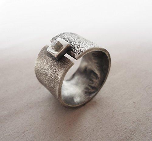 Anillo de plata ancho con diamante en bruto.