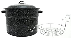 A black canning kettle with a wire rack next to it.