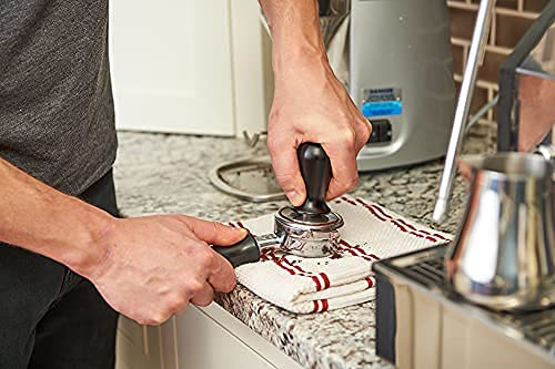 a person leveling the espresso grounds on a portafilter