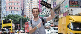 A male entrepreneur holding a product he created on a busy city street.