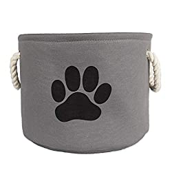 a grey cloth pet toy storage bin with a black puppy paw and white rope handles