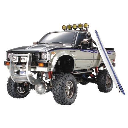 TAMIYA 1:10 RC Toyota HiLux HighLift 4x4 3-Gang - ferngesteuertes Auto - inkl. Surfbrett - Offroad - Pick Up -Elektromotor - Modellbausatz - Metallgetriebe - unlackiert - 58397