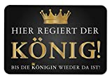 Tassenbrennerei Fußmatte mit Spruch Hier regiert der König - Bis die Königin Wieder da ist - Fußabtreter lustig, Türmatte waschbar - Originelles Geschenk (Schwarz)