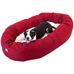 Brown and white dog laying in a red bagel shaped dog bed.