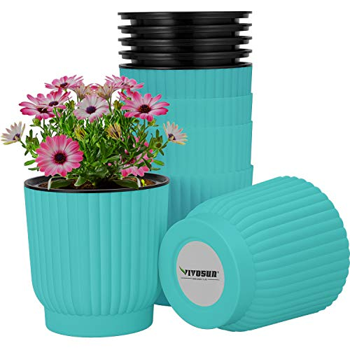 teal pot with pink flowers in it, a teal pot on it's side next to it and a stack of teal pots behind.