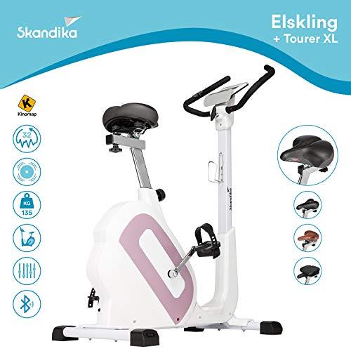 skandika Elskling - Vélo d'appartement - Differentes selles - 24 Prog. - 32 Niveaux de résistance - Frein magnétique - Inertie 11 kg - Bluetooth + Appli. (Rose avec Selle Randonnée)