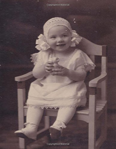 Smiling Little Girl Sitting in a Little Wooden Chair: Baby fashion of yesteryear. This photo was circa 1907.