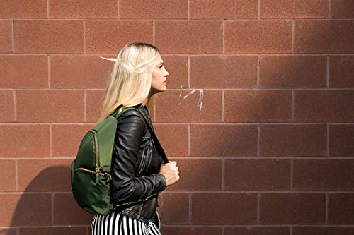 Woman walking in front of a brick wall with an anti theft backpack slung over her shoulder.