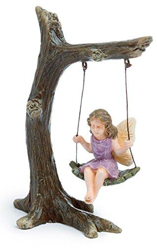 Figurine fée sur balançoire tronc d'arbre