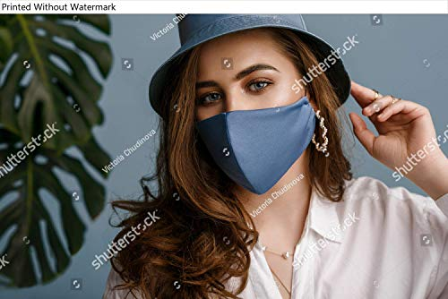 Poster of Woman wearing stylish outfit with luxury designer protective blue face mask, bucket hat, pearl earrings. Trendy Fashion accessory during quarantine of coronavirus pandemic. Close up
