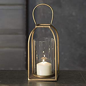 "Measurement: Decorative Gold- Antique Brass metal Lantern Candle Holder with glass chimney is made of metal and measures 5½""W x 5½""D x 14¼""H. Show with a 3"" candle, not included. Color: Gold lantern with clear glass. A WARM, WELCOMING GLOW FOR VISITO..."