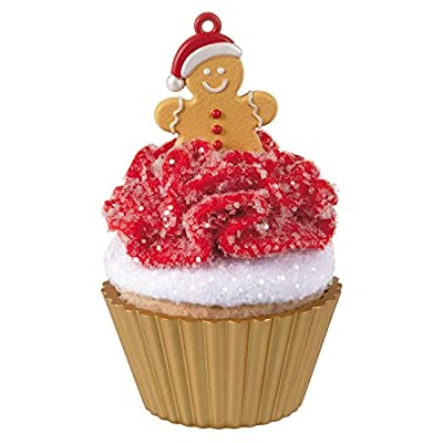 Cupcake in brown liner decorated with glitter red and white icing with a cute gingerbread man on top
