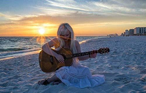Chica tocando la guitarra en la playa junto al mar, brillando la...