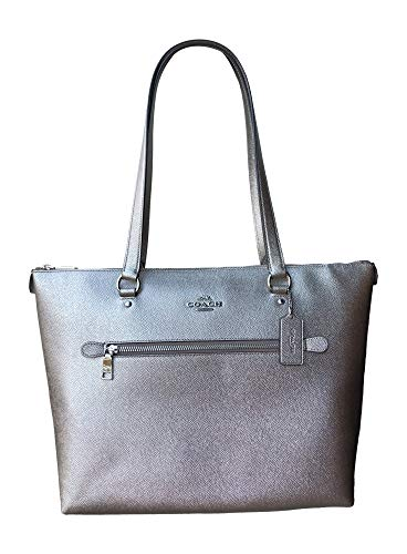 """Metallic leather with silver tone hardware Exterior zip pocket; handles with 10"""" drop Raised silver tone Coach logo on front Interior features fabric lining with one zip pocket and two multifunction slip pockets; Coach leather license with model numb..."""
