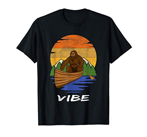 Bigfoot en una canoa, VIBE. Montaña Atardecer Retro Vintage Camiseta