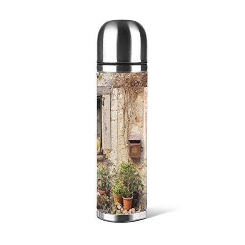 Puerta de botella de agua de acero inoxidable de una casa de roca antigua con detalles de marco francés en el campo europeo pasado con aislamiento al vacío de cuero a prueba de fugas de doble pared contenedor de viaje termo de 500 ml