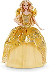 In glistening gold from head to toe, 2020 Holiday Barbie doll sparkles with the wonder of the season. Her gown dazzles with a glittering golden bodice, bow-detailed belt and a tulle skirt with a shimmering snowflake-printed overlay. Long blonde waves...