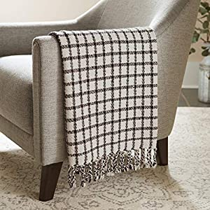 "Imported Add some simple sophistication to your living room comfort with this elegant throw blanket. The black and ivory grid creates a clean, eye-catching style, and a row of twisted tassels on either end complete this fun and versatile design. 60""L..."