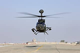 Posterazzi PSTTMO100180MLARGE An OH-58D Kiowa Warrior hovers over the flight line at Camp Speicher Iraq Poster Print 34 x 23