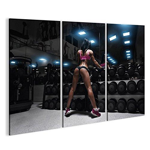 islandburner Bild Bilder auf Leinwand Rückansicht der sexy Junge Brünette Frau ruht in der Turnhalle und lehnt auf Reihe von Hanteln. Fitness Mädchen in Fitnessstudio in einem blau