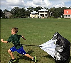 Young boy running on grass with a 48 Inch Sports Power Running Chute Parachute dragging behind him