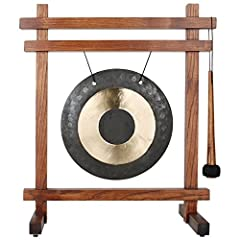Desktop gong includes a beautiful brass tabletop-sized gong, teak stained ash wood stand and mallet Stands 19-inches tall x 16-inches wide; 10-inch diameter brass and Black bulls-eye gong Woodstock Gongs are hand-hammered by a master gong maker and m...