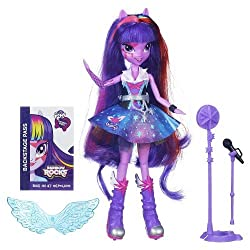 A fashion doll with a toy microphone beside her.