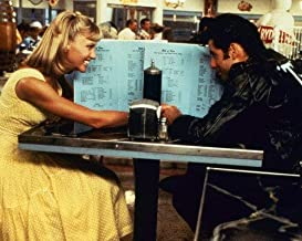 John Travolta and Olivia Newton-John in Grease seated in diner hiding behind menus 8x10 Promotional Photograph