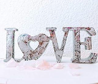 Orgonita letrero love en tonos rosas y plateado con virutas de aluminio y Piedra semipreciosa llamada: Cuarzo rosa.