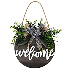 """Design — Our """"welcome"""" wooden sign is designed by our """"POETIC WREATH"""" professional design team through continuous efforts to improve and innovate. Craft — Artificial green plants and beautiful bows are manually glued on the """"welcome"""" round wooden pla..."""