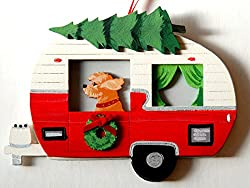 A Christmas ornament of a vintage-style trailer with a Goldendoodle looking out the window, photo