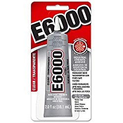 E6000 - Strong holding glue will attach metal to glass.