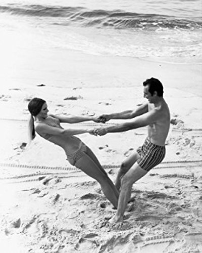 Young couple swinging each other on the beach Poster Drucken (45,72 x 60,96 cm)