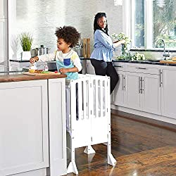 child on learning tower in kitchen