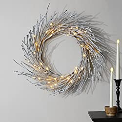 view of white winter decor wreath with twinkly lights