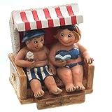 Dio Fröhliches Urlauberpaar im Strandkorb mit Eis und Buch