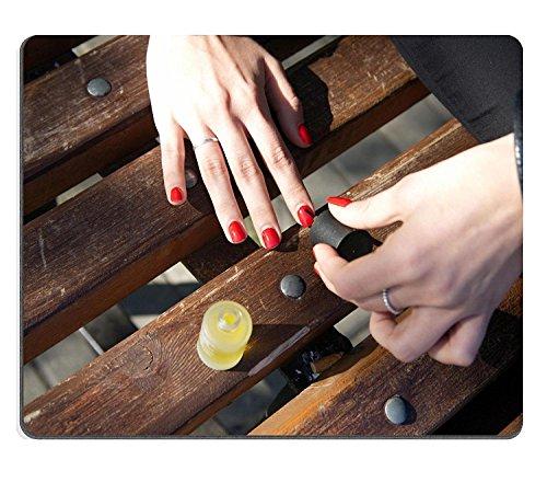 Luxlady Gaming Mousepad IMAGE ID: 31675085 Handen van een jong meisje die een manicure maakt met rode nagellak zittend buiten op een bank Photo Close up