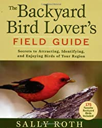 Scarlet tanager on front of field guide