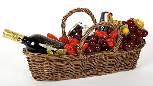 Cesta de Frutas Para Él, con frutas tropicales, mermelada, rulo de queso de cabra y botella de vino, sobre una cesta de mimbre.