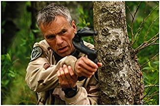 Stargate Richard Dean Anderson as Col. O'Neill aiming weapon from behind tree 8 x 10 Inch photo