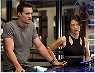 Agents of S.H.I.E.L.D. (8 inch by 10 inch) PHOTOGRAPH Brett Dalton in Grey Tee Shirt Next to Ming-Na Wen in Sexy Cutout Out Sleeveless Top at Table Pose 2 kn