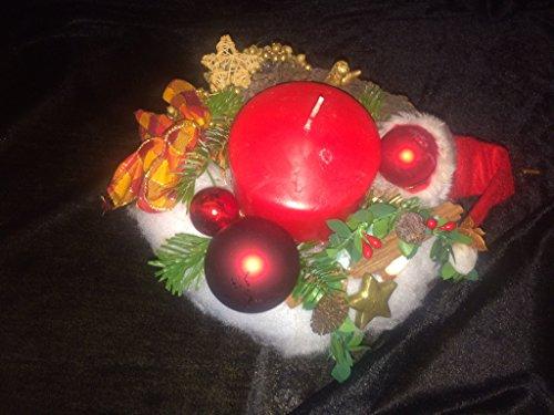 Adventsgesteck mit einer roten Kerze auf einem roten Porzellanteller mit Fuß
