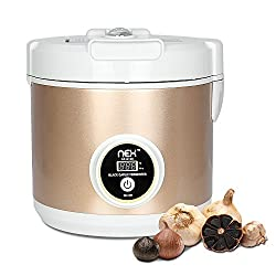 A black garlic fermenter with several heads of black garlic in front of it.