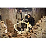 Bones Emily Deschanel as Dr. Brennan Holding Flashlight Leaning Over Skeleton Posed on Brick and David Boreanaz as Special Agent Booth Standing in Trench Coat 8 x 10 Photo